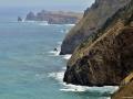 Strmé útesy Madeiry bičují vlny Atlantiku a v pozadí mys Ponta de Sao Lourecno.